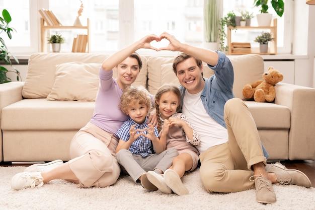 Gelukkige ouders en twee schattige broers en zussen zittend op de vloer door de bank voor camera en hartvorm met vingers maken