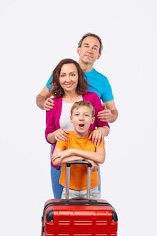 Gelukkige ouders en zoon die naar de camera kijken terwijl ze achter de koffer staan voor de zomerreis tegen een witte achtergrond