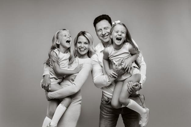 Gelukkige ouders houden hun kinderen in hun armen en glimlachen op een gele achtergrond. een emotioneel gezin van vier.