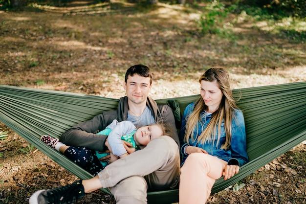 Gelukkige ouders in een hangmat met hun baby buitenshuis