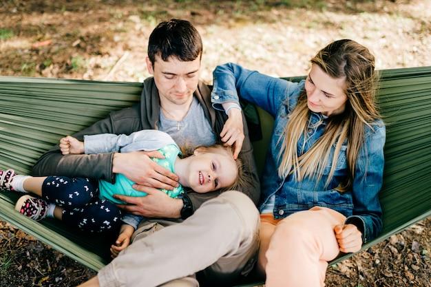 Gelukkige ouders in hangmat met hun baby buitenshuis