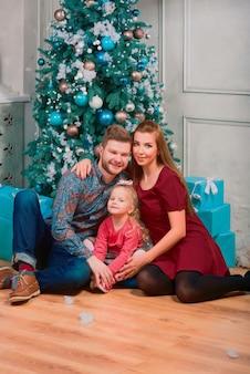 Gelukkige ouders knuffelen hun schattige blonde dochter in de buurt van nieuwjaarsboom