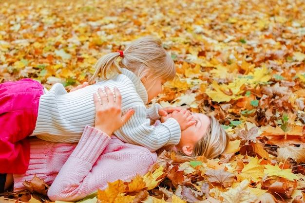 Gelukkige ouders met baby op de natuur in het herfstpark