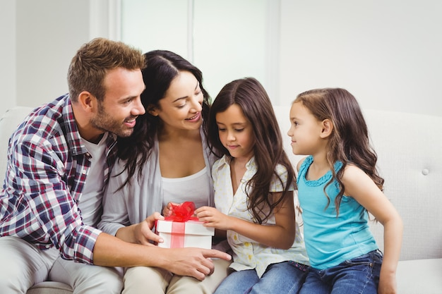 Gelukkige ouders met hun dochters die een geschenkdoos houden