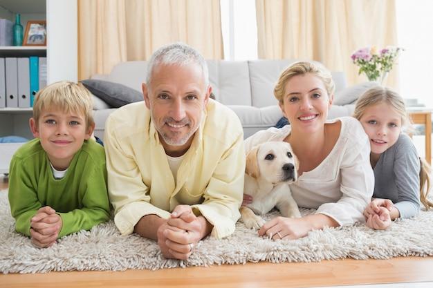 Gelukkige ouders met hun kinderen en puppy op vloer