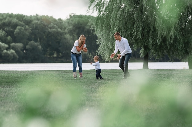 Gelukkige ouders met hun zoontje wandelen samen in het voorjaarspark. het concept van gezinsgeluk