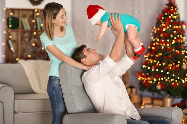 Gelukkige ouders met kleine baby in versierd voor kerstkamer