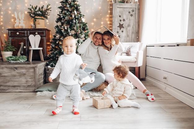 Gelukkige ouders onder dak gemaakt van open laptop kijken naar hun spelende kinderen. kersttijd.