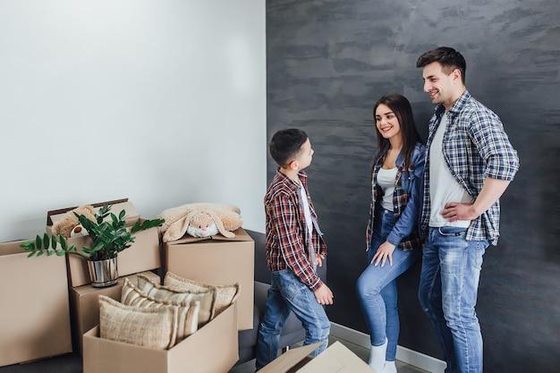 Gelukkige ouders praten met zoon in nieuw huis