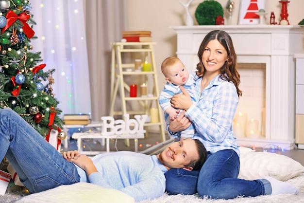 Gelukkige ouders spelen met baby op de vloer in de versierde kerstkamer