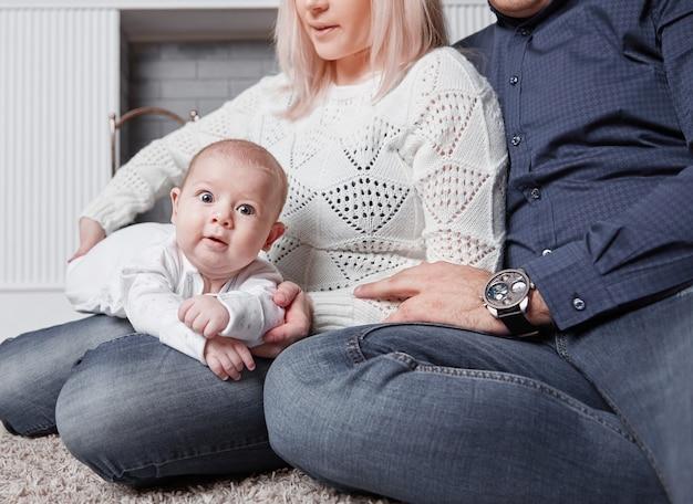 Gelukkige ouders spelen met hun baby bij de open haard in de woonkamer