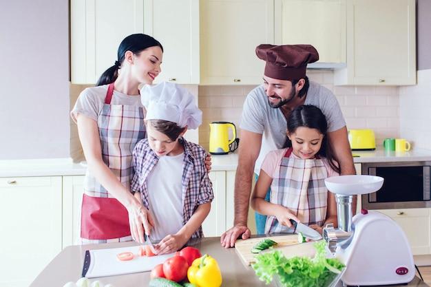 Gelukkige ouders staat achter hun kinderen en lachend.