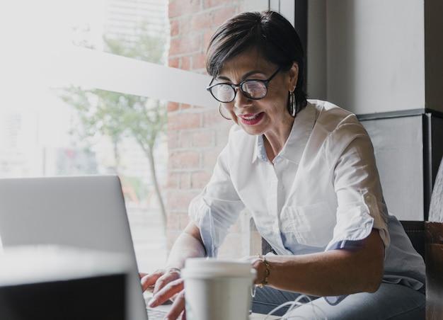 Gelukkige oudste met oogglazen die aan laptop werken