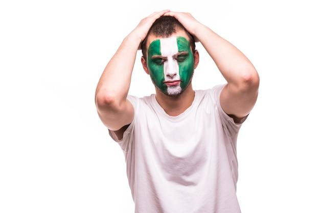 Gelukkige overwinning schreeuw man fan steun nigeriaans nationaal team met geschilderd gezicht geïsoleerd op een witte achtergrond