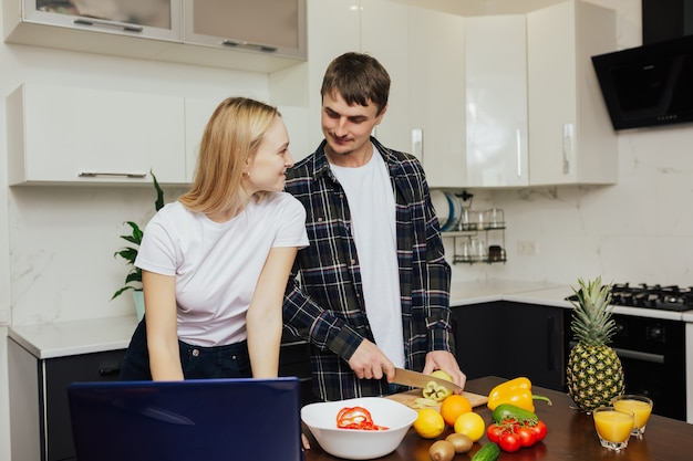 Gelukkige paar bereiden van gezond diner samen in hun keuken thuis.
