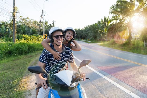 Gelukkige paar berijdende motorfiets in platteland opgewekte vrouw en man reis op de reis van de motorweg