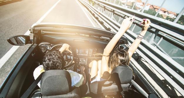 Gelukkige paar converteerbare auto rijden op de weg - vriend en vriendin plezier op vakantie - vriend en vriendin genieten van zonsondergang rijden in klassieke sportwagen - transportconcept