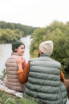 Gelukkige paar die elkaar dichtbij rivier bekijken