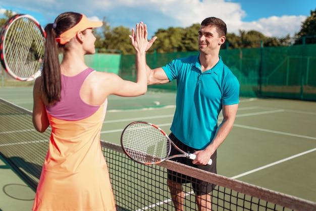 Gelukkige paar die met rackets op openluchttennisbaan spelen.
