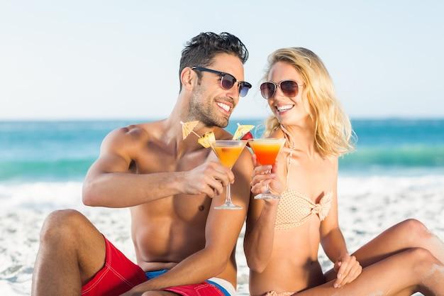Gelukkige paar die rijtjes cocktail zitten drinken