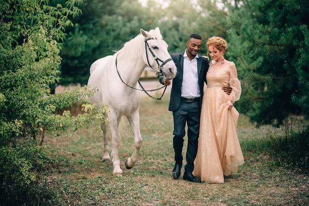Gelukkige paar die samen op boerderij met paarden bij zonsondergang lopen
