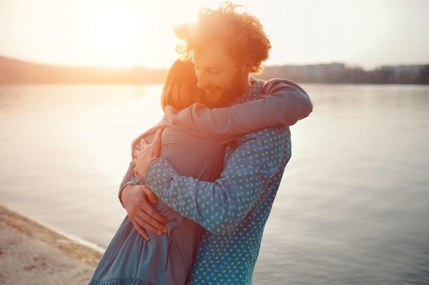 Gelukkige paar elkaar knuffelen op een zonnige dag in de buurt van het meer
