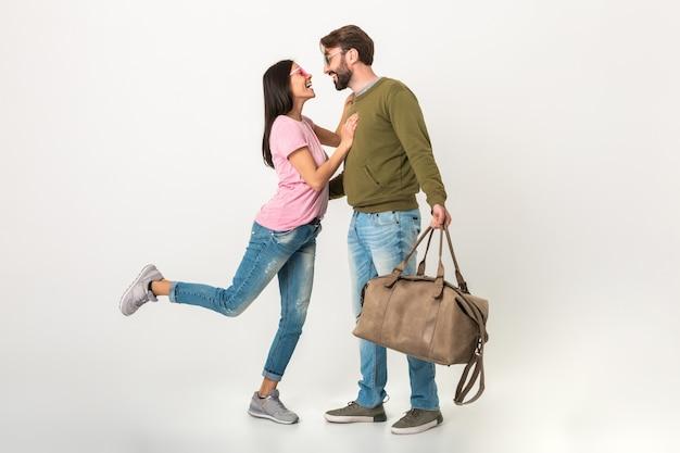 Gelukkige paar geïsoleerde, mooie lachende vrouw in roze t-shirt ontmoeting man in sweatshirt met reistas na een reis, gekleed in spijkerbroek, romantische liefde