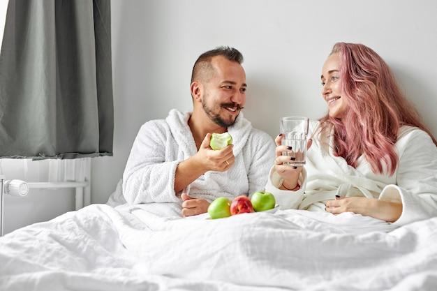 Gelukkige paar genieten van ontbijt op bed, ze lachen terwijl ze verse appels eten