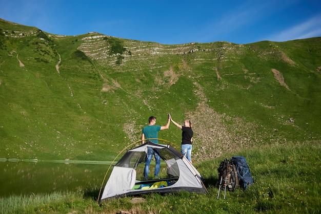 Gelukkige paar geven high five in de buurt van kamperen met een tent