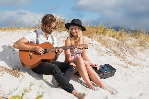 Gelukkige paar gitaarspelen op strand
