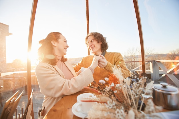 Gelukkige paar hand in hand en glimlachen naar elkaar hebben een date op een prachtige plek in het restaurant