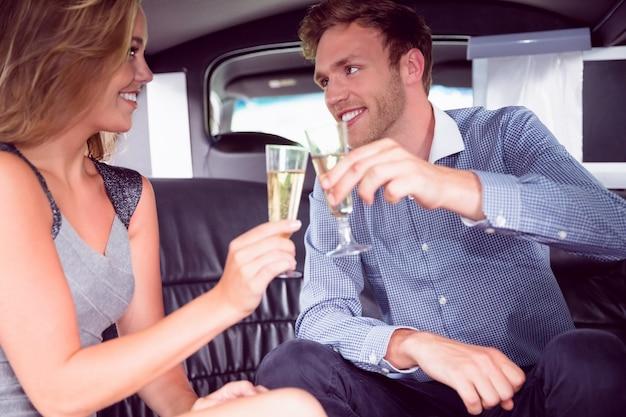 Gelukkige paar het drinken champagne in limousine