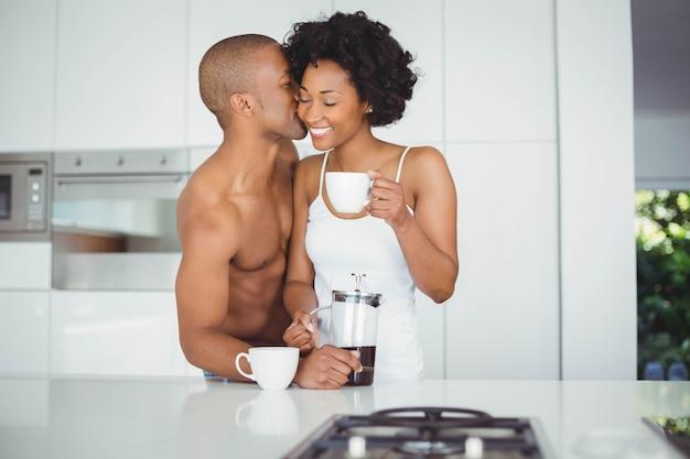 Gelukkige paar het drinken koffie in de keuken thuis