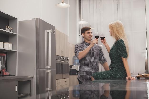 Gelukkige paar het drinken wijn samen thuis