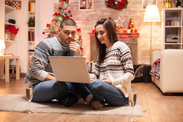 Gelukkige paar in bijpassende kleding doen online winkelen voor kerstmis op laptop.
