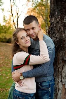 Gelukkige paar in herfst park. vallen. jong gezin plezier