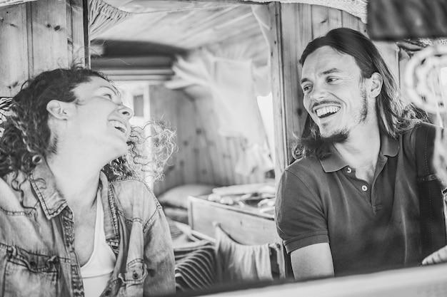 Gelukkige paar in minibus die een roadtrip doet tijdens de zomervakantie - focus op het gezicht van de man