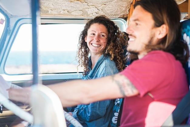 Gelukkige paar in minivan doet een road trip - vrouw met sproeten plezier op zomervakantie reizen met haar vriendje