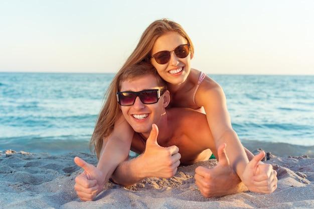 Gelukkige paar in zonnebril plezier op het strand