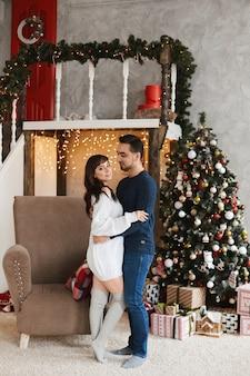 Gelukkige paar jonge geliefden knuffelen terwijl ze poseren in de buurt van de kerstboom in de woonkamer versierd met...