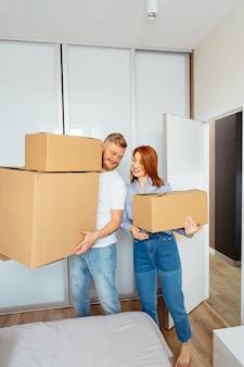 Gelukkige paar kartonnen dozen houden en verhuizen naar nieuwe plek