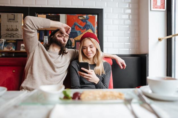 Gelukkige paar kijken naar telefoon in café