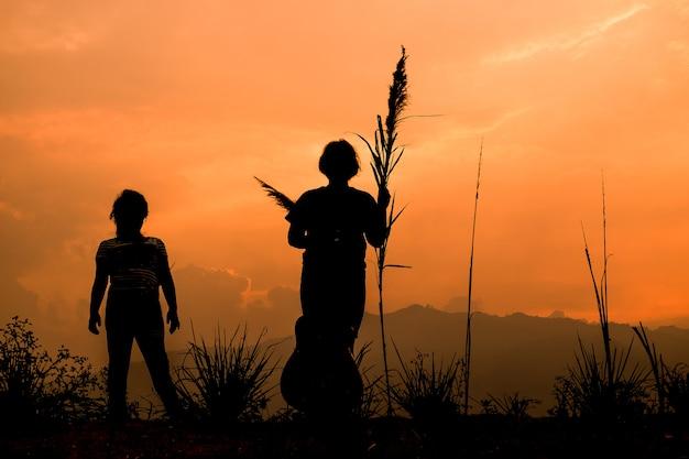 Gelukkige paar kinderen spelen op weide bij zonsondergang, silhouet