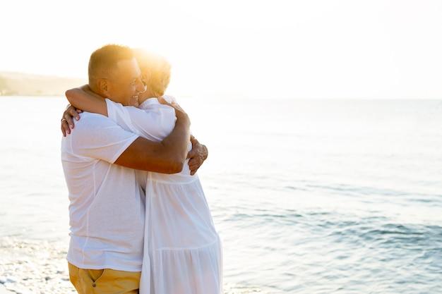 Gelukkige paar knuffelen aan zee