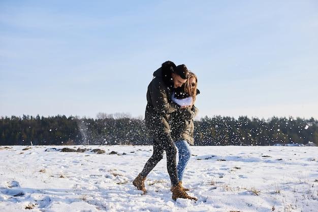 Gelukkige paar knuffelen en lachen buiten in de winter.