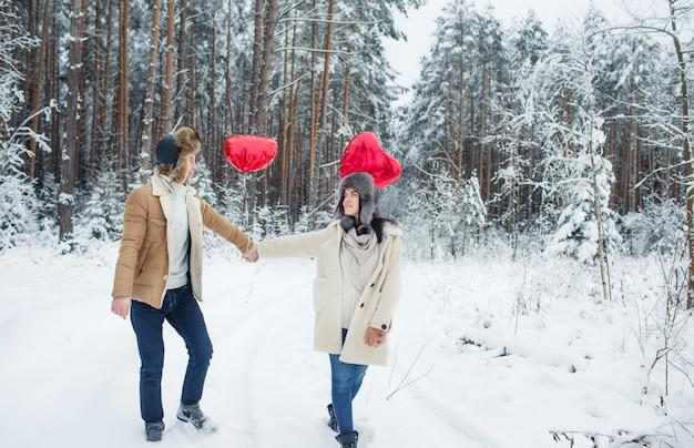 Gelukkige paar knuffelen en zoenen buiten in de winter woud. ballonnen in de vorm van een hart