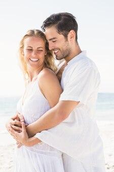 Gelukkige paar knuffelen op het strand