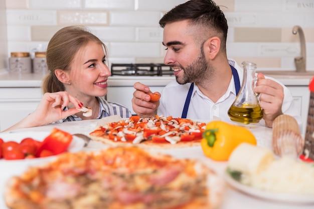 Gelukkige paar kokende pizza met tomaten en paddestoelen