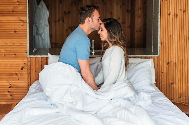 Gelukkige paar kussen in bed