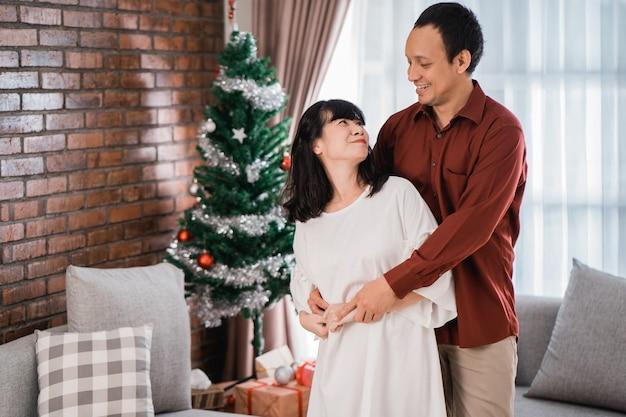Gelukkige paar liefdevolle elkaar dansen tijdens kerstdag thuis